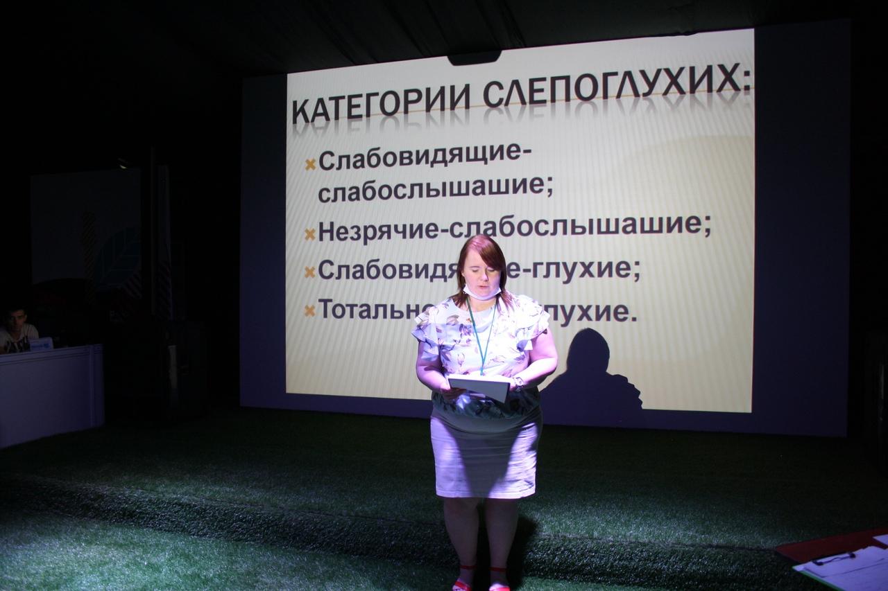 Цветная фотография, молодая девушка читает доклад на фоне презентации