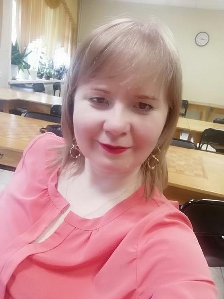 Цветная фотография, на ней молодая девушка блондинка, в розовой блузке на фоне кабинета. Слева от неё на окне цветы, на стене за ней круглые часы.